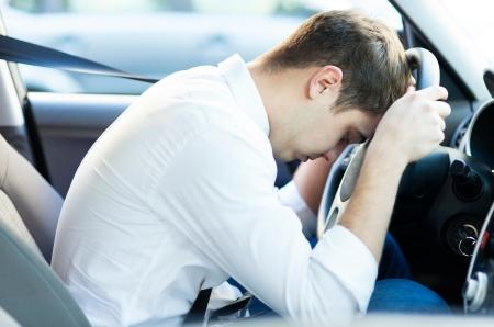 chofer: Conductor agotado descansando en el volante Foto de archivo