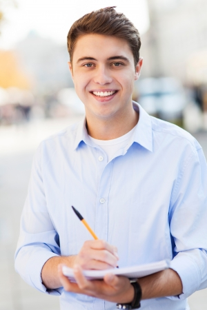 Male student with pen and notebook photo