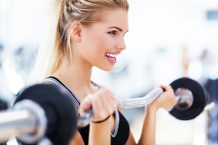 levantando pesas: Mujer en el gimnasio levantando pesas Foto de archivo