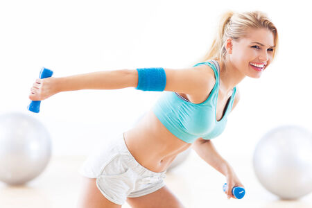 Woman in gym exercising with dumbbells photo