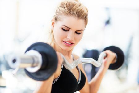 lifting weights: Mujer en el gimnasio levantando pesas Foto de archivo