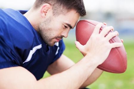 American footballer holding ball photo