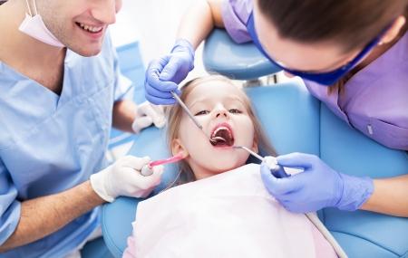 examined: Girl having teeth examined at dentists