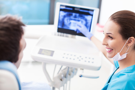 x ray equipment: Dentist explaining x ray picture to patient Stock Photo