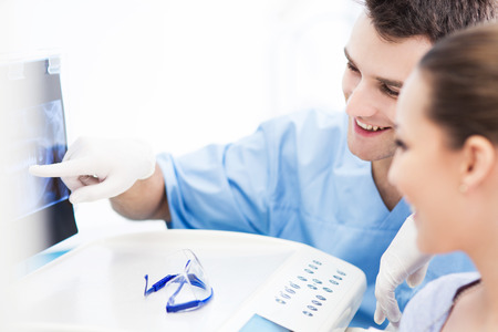 dentist at work: Dentist explaining x ray picture to patient Stock Photo