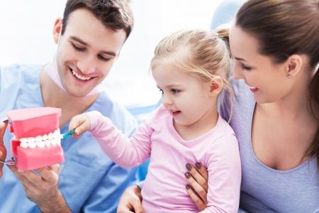 양치질하는 방법을 가르치는 여자 치과 의사