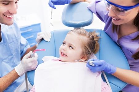 odontologia: Muchacha que tiene dientes examinados a los dentistas