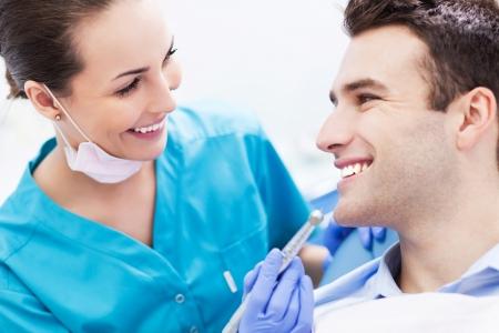 Femme dentiste avec le patient mâle