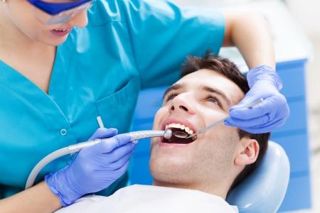 Hombre que tiene dientes examinados a los dentistas