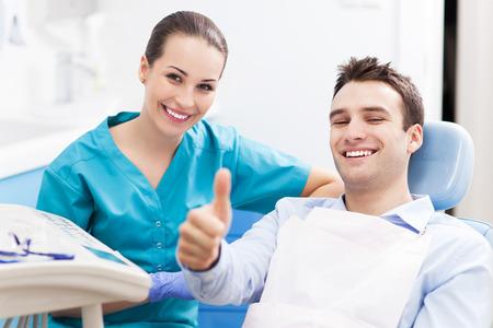 odontologia: Hombre que da los pulgares para arriba en la oficina del dentista Foto de archivo