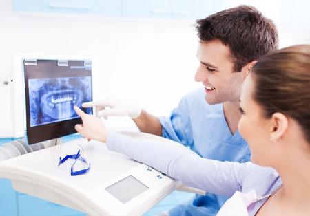dentista: Dentista que muestra las radiograf�as con el paciente