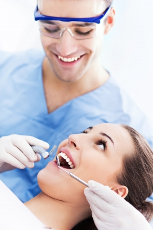 tooth cleaning: Male dentist with female patient Stock Photo