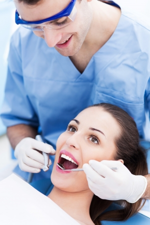 Male dentist with female patient photo