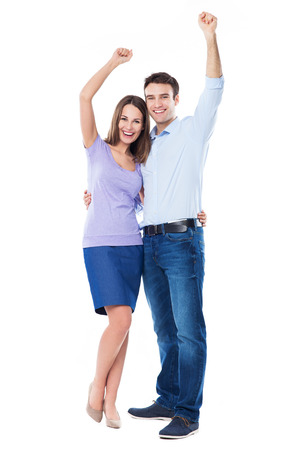 Young couple with arms raised