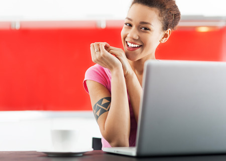 Smiling african american woman with laptop photo
