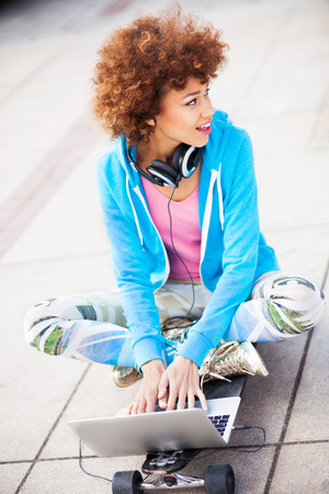 Funky woman sitting on skateboard with laptop photo