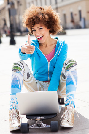 Urban woman with laptop and thumbs up photo