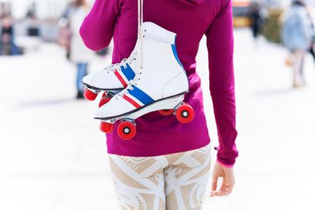 rollerskates: Woman holding roller-skates