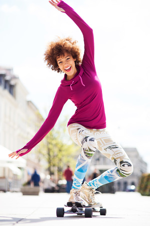 happy african woman: Young woman skateboarding