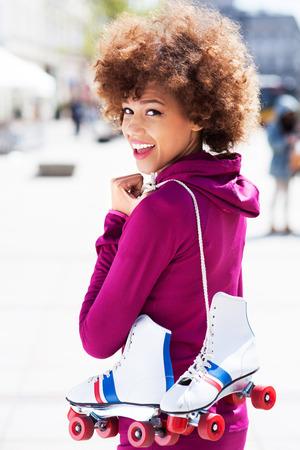 rollerskates: Afro-American woman holding roller-skates