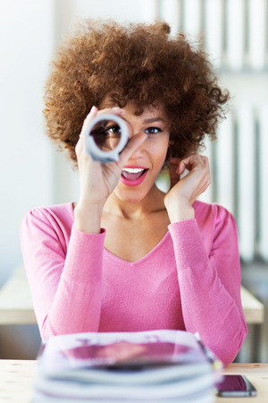 Afro woman using newspaper as spyglass photo