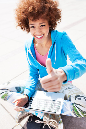 Afro woman with laptop and thumbs up photo