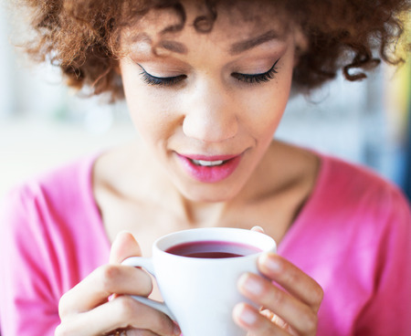 Afro woman with cup of tea Standard-Bild