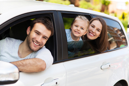 woman driving car: Family sitting in the car looking out windows Stock Photo