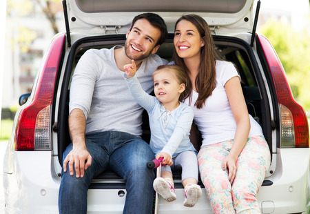 woman driving car: Happy family sitting in the car