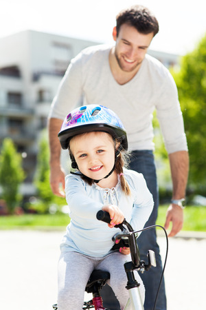 Little girl learning to ride a bike with her father photo