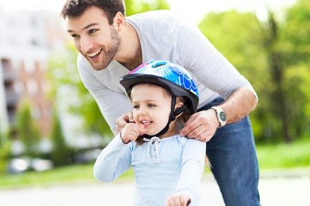 Padre ayudando a su hija con el casco de la bici Foto de archivo - 28381911