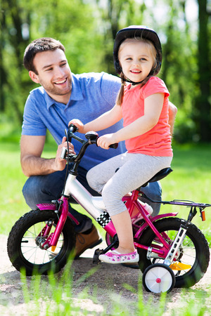 family day: Little girl learning to ride a bike with her father Stock Photo