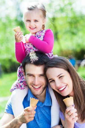 eating ice cream: Familia feliz que come el helado Foto de archivo