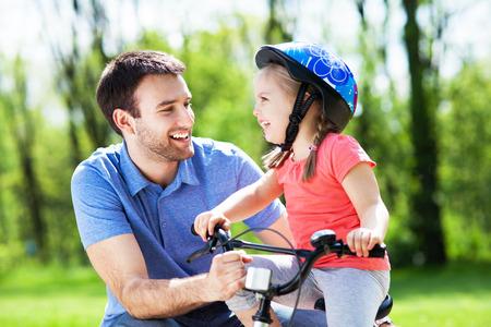 dadã  daughter: Muchacha que aprende a andar en bicicleta con el padre Foto de archivo