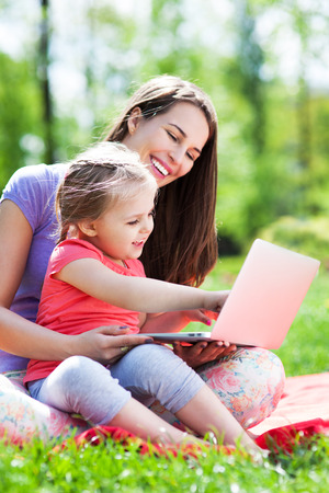 Mother and daughter using laptop outdoors photo