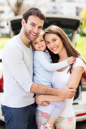 Happy family with car on background Stock Photo