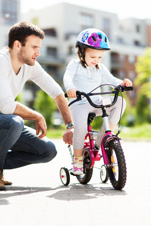 Girl learning to ride a bicycle with father photo