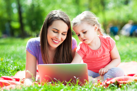 Mother with child using laptop outdoors photo