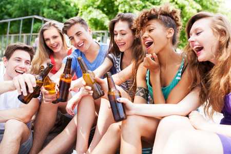 Group of friends sitting with beers in their hands Stock Photo