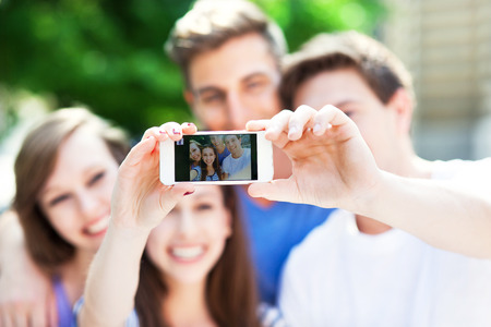 Friends taking a selfie with smartphone photo