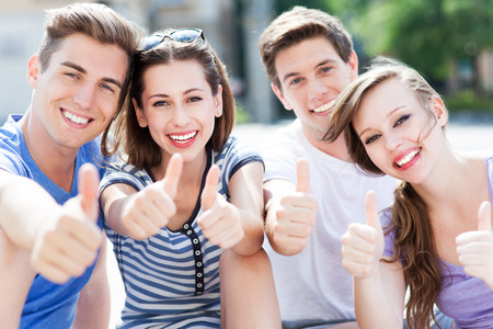 Young people with thumbs up Stock Photo