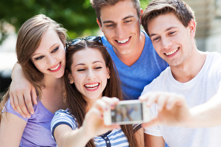 teenagers standing: Friends taking photo outside