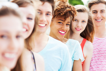 multi ethnic: Friends in a row smiling