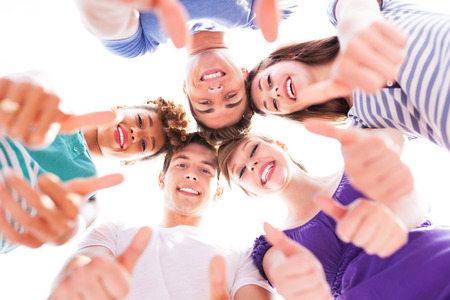 girl bonding: Young people with thumbs up Stock Photo