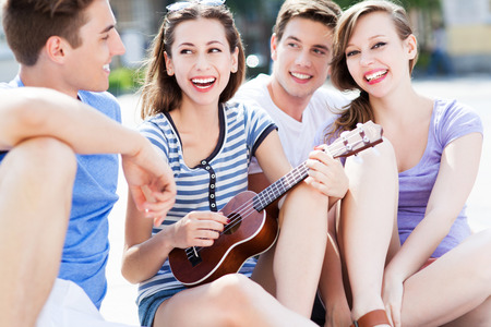 Young woman playing ukulele for friends Stock Photo