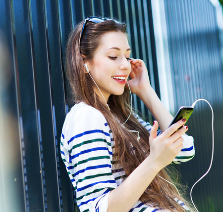 Young woman listening to music with smartphone