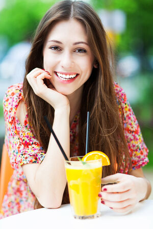 Woman drinking orange cocktail photo