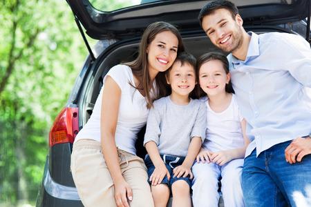 aandrijvingen: Gelukkig gezin van vier zitten in de auto kofferbak