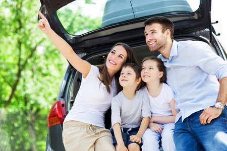 day trip: Happy family of four sitting in car trunk  Stock Photo