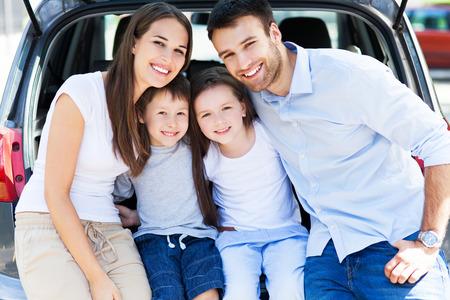 familia viaje: Feliz familia de cuatro sentado en el tronco de coche